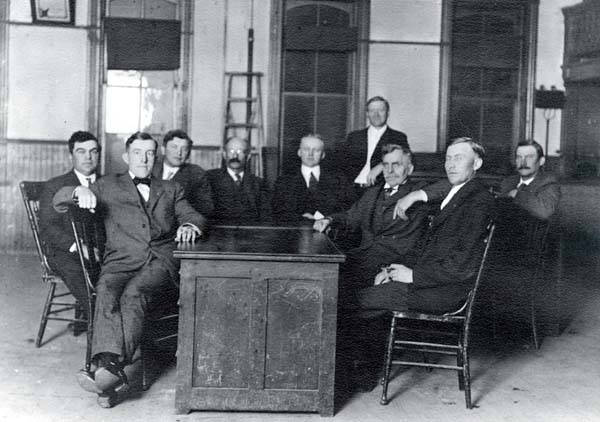 A Niles Center Village Board of Trustees meeting in the old firehouse, sometime between 1919 and 1920.  Members, seated left to right:  Christian Blameuser, Robert Hoffman, Albert Lies, Samuel Meyer, George H. Klehm (Mayor), John W. Brown Sr., Richard Kruse, Charles Langfield (Clerk); standing is an unidentified legal or engineering consultant